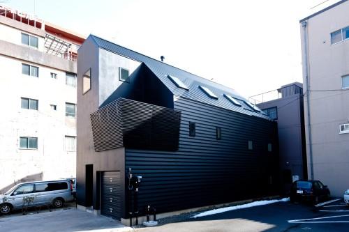 3階建てのビルトインガレージを持つ黒い外観の家