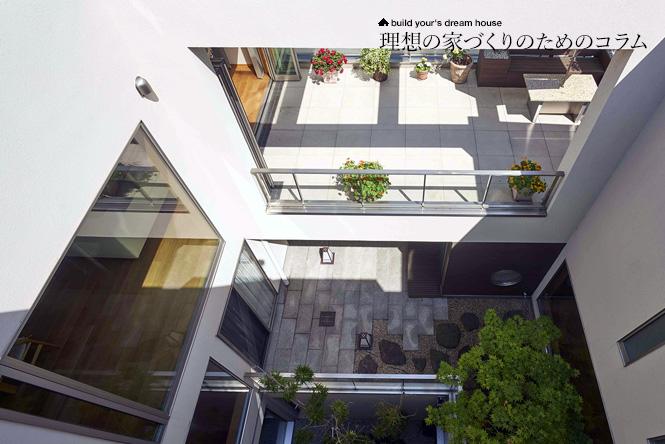 中庭とテラスを見渡せる白を基調とした3階建て住宅