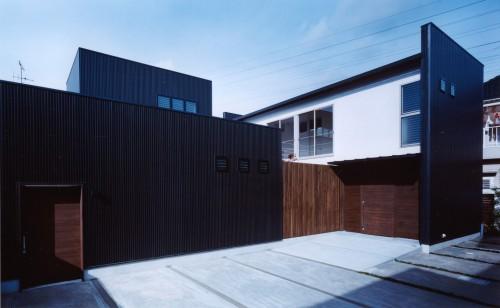 玄関廻りは板貼りで、ガルバリウム鋼板スパンドレルの外壁を持つ住宅