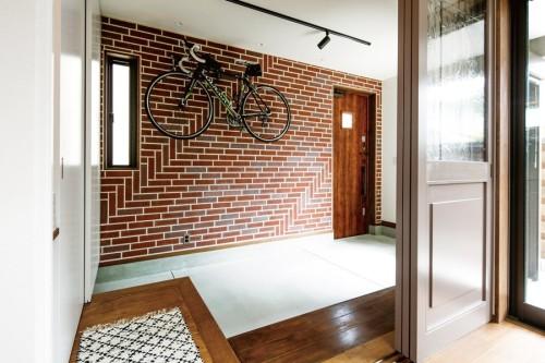 趣味の自転車を掛けられるレンガタイルのある土間玄関