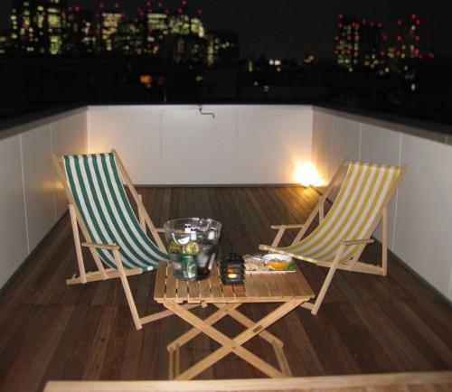 ウッドデッキ敷かれた屋上の夜景とテーブルとチェア