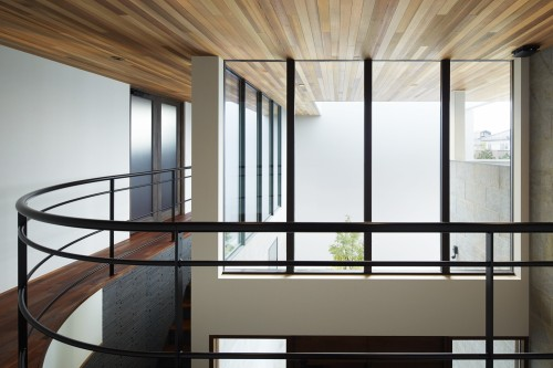 室外へ天井の板貼りが伸びる廊下の吹き抜け