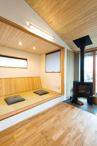 シンプルな薪ストーブのある畳スペースの和室