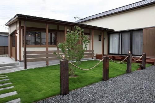 芝生の庭と木製の格子のある平屋風住宅