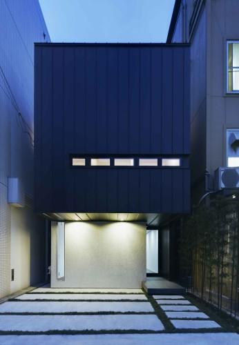 1階はグレー、2階はキューブ型の黒い板張りの狭小住宅