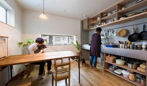 小物が整理された使い勝手の良いキッチンと木のダイニングテーブル
