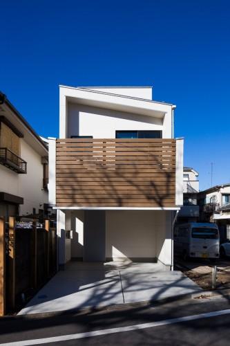 白い外壁に木製ルーパーがアクセントの狭小住宅