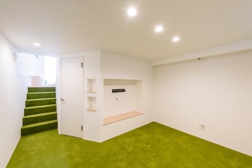 白い壁と緑の絨毯がアクセントになっている地下室