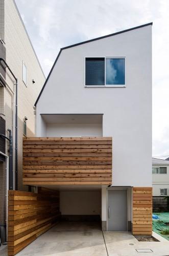 白い外壁に木目のバルコニーが映える狭小住宅