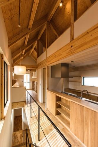 吹き抜けに面した木製のキッチンカウンター