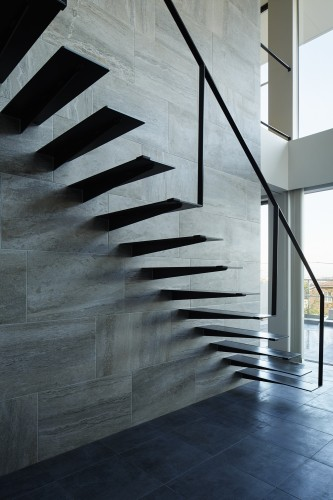 石貼りの壁から伸びるスチール製のリビング階段