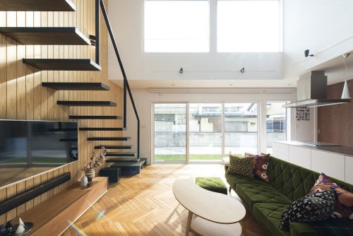美しい板張りの壁と片持ち階段のリビングダイニング