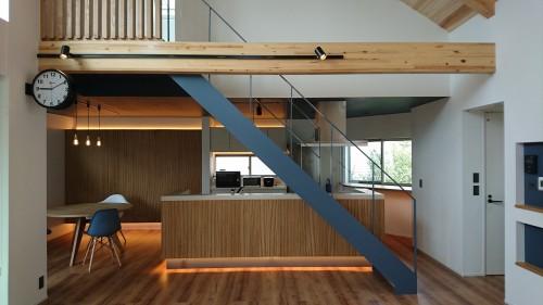 木目のキッチンとブルーの映える鉄骨階段