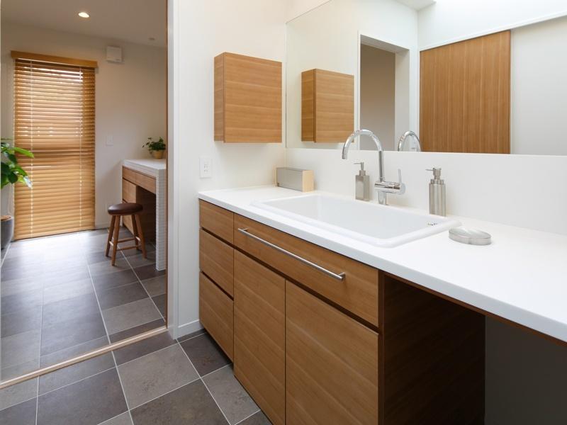 木製の扉付き収納のあるタイル床の洗面所