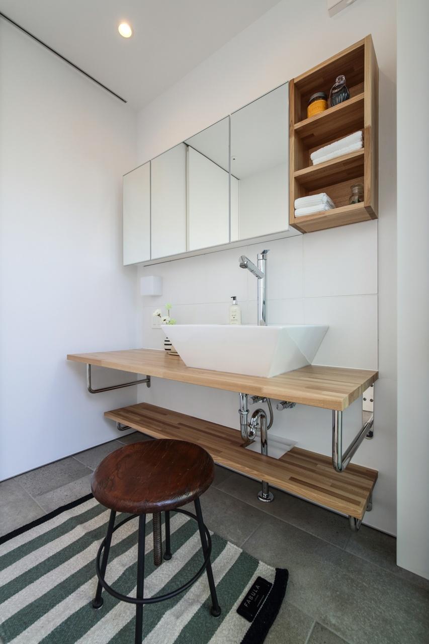 ミラーキャビネットと木製の収納のある洗面所