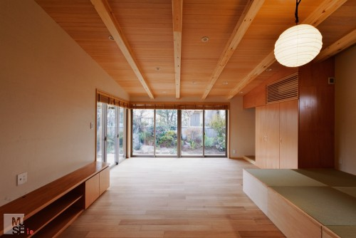 あらわしの梁と羽目板張りの天井のリビング