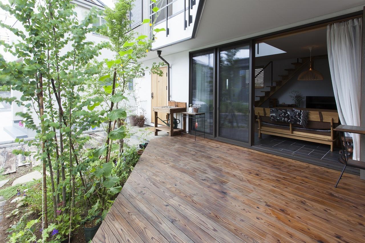 背の高い植栽のある庭へ繋がるウッドデッキ