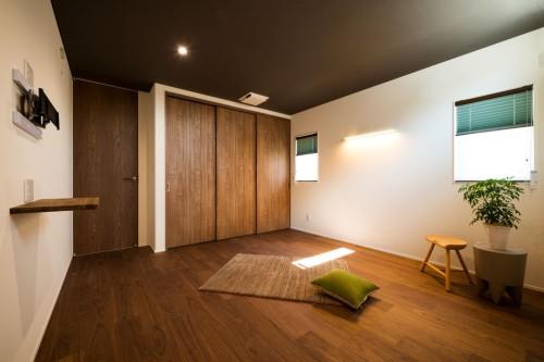 黒の平天井とフローリングの寝室