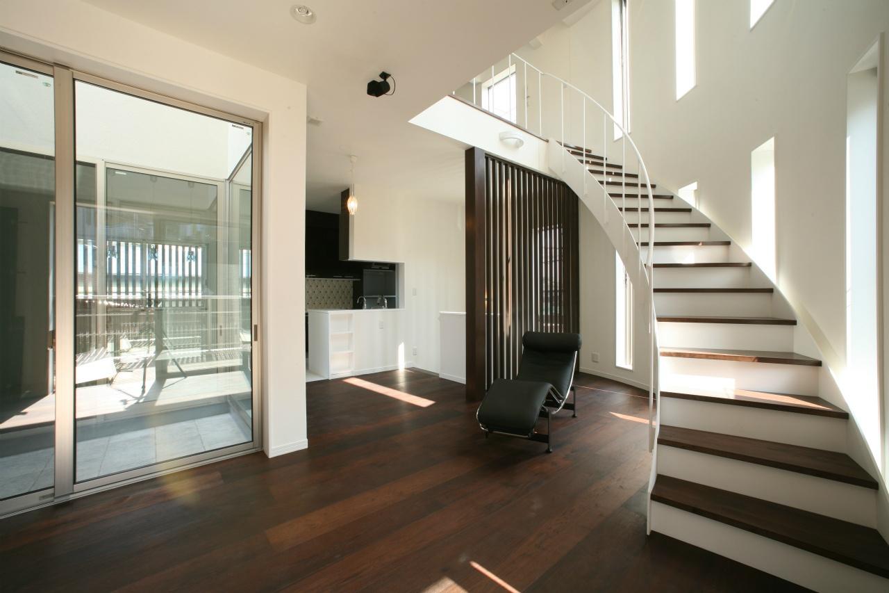 曲線の壁に沿って二階へと上るリビング階段は、まさにこの空間の主役的な存在
