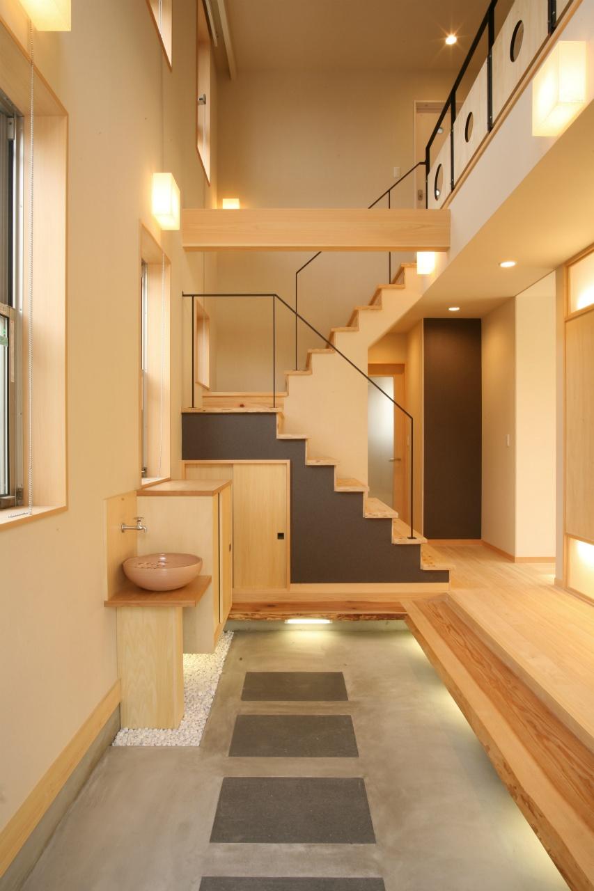 間接照明を使った温かみのある玄関空間。ヒノキの天然木を使った上がり框を一段設け、ベンチのような感覚で使うことができます。