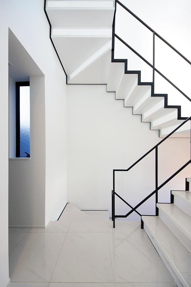 白いスタイリッシュなタイルの床に白い階段を組み合わせた、究極にシンプルでモダンな階段