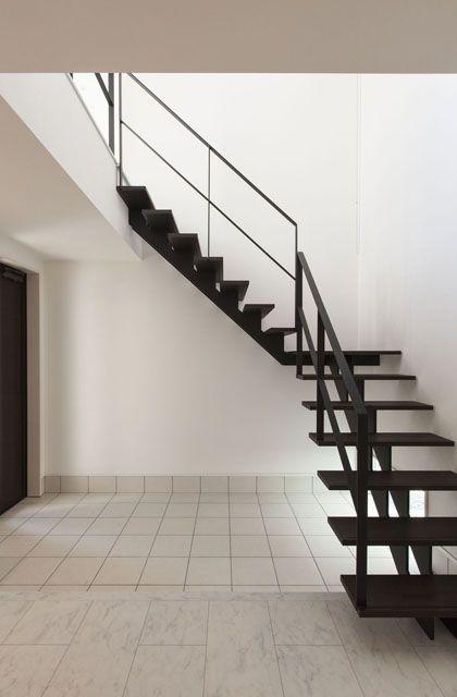 吹き抜けのエントランスには、家のシンボルにもなる印象的な黒い階段を