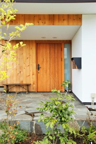 石畳があり白い壁にレッドシダーの板張りの玄関