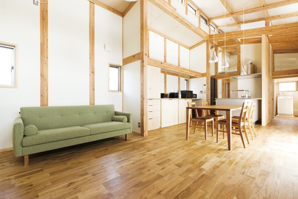 薄いグリーンのソファの置かれた天井の高いリビングダイニング