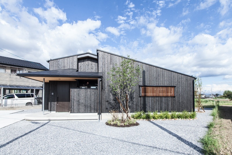 黒い板張りの平屋風の2階建の家