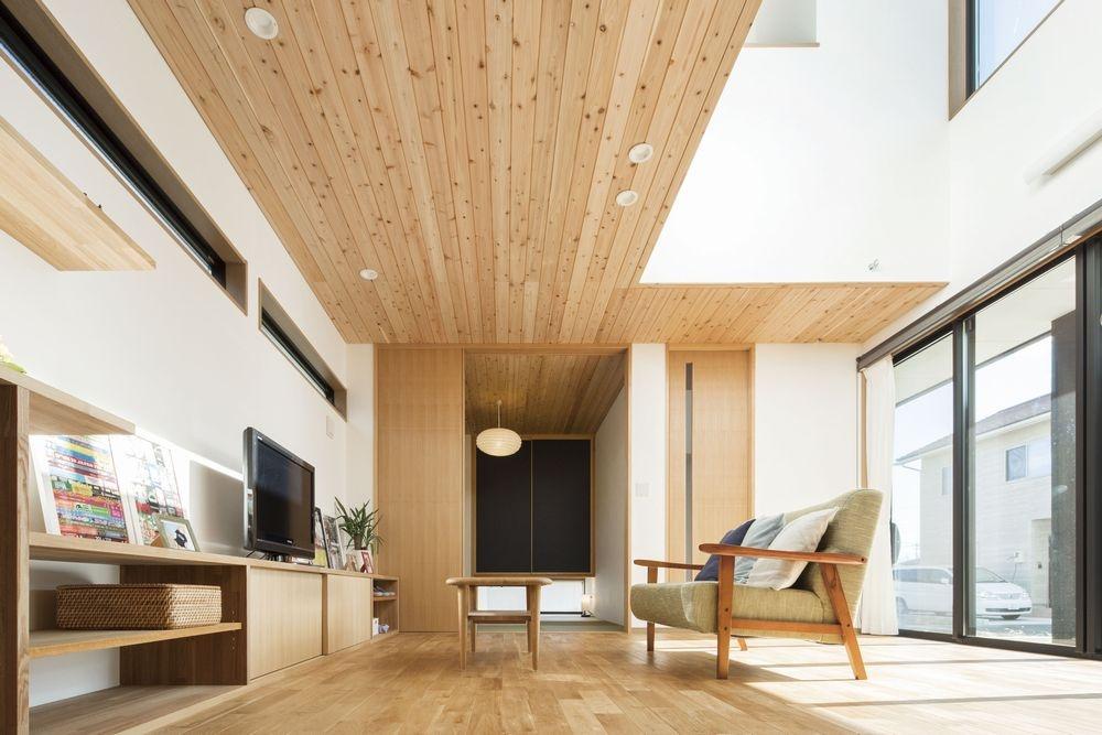 杉板の天井と木材の家具の置かれた日当たりの良いリビング
