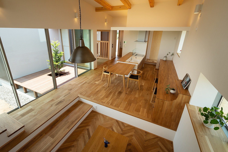 木の床や家具が統一感のある、スキップフロアを設けたリビングダイニング