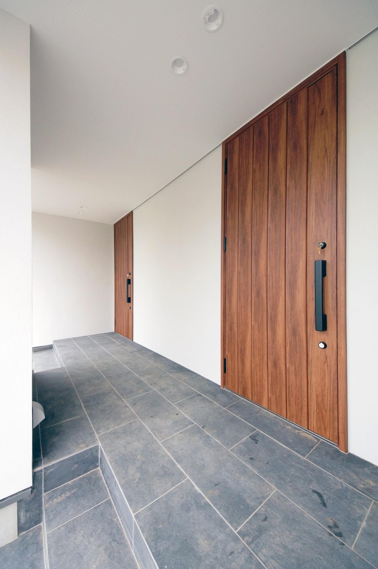 木製の玄関扉が二つ並んだアプローチ