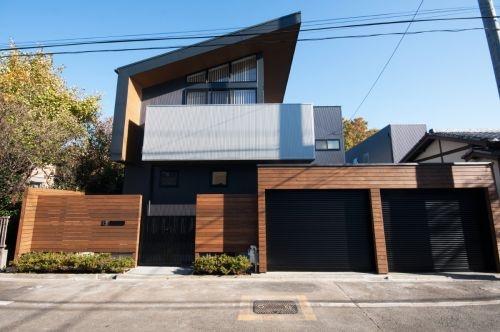 木製の塀とグレーの壁を持つ家