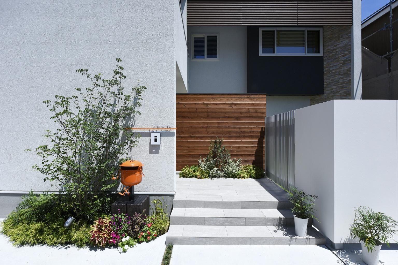 白い外壁と階段のある植物が植えられた家