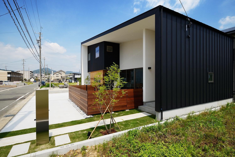 黒い壁面を持つ、木の塀のある家