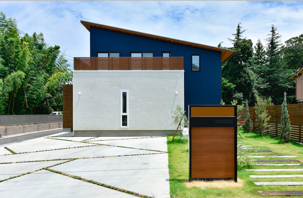 木製の門柱と芝生、駐車スペースのある家
