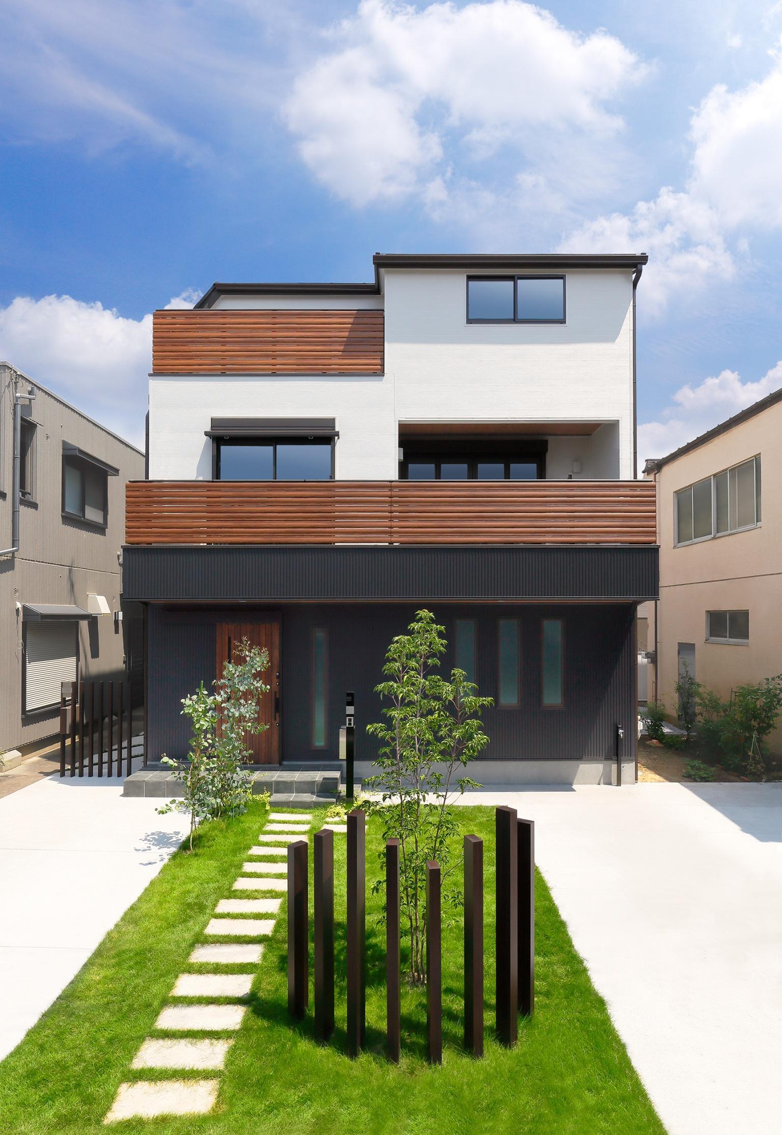 芝生と飛び石の敷かれた2階建ての家