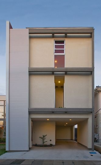 箱型のベージュ外壁と窓を持つ外観の住宅