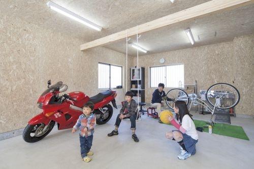 バイクと自転車のあるビルトインガレージで遊ぶ子供達
