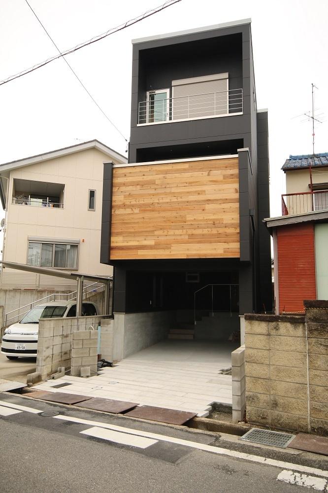 箱型の黒い外壁と木目の外観を持つ住宅