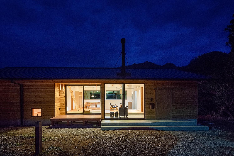 木の壁と大開口とウッドデッキのある平屋