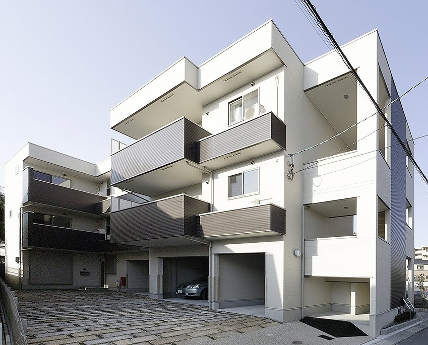 白い壁の3階建ての家賃貸住宅